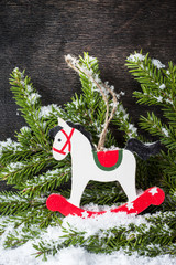 Christmas rocking horse and spruce branches with snow.