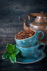 Roasted coffee beans with green leaves in cups and vintage pot