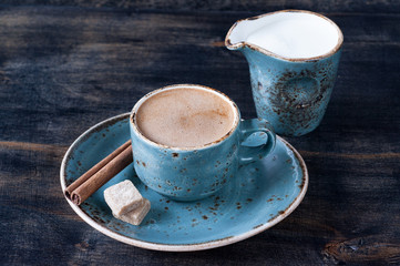 Cup of coffee with milk, cinnamon and sugar