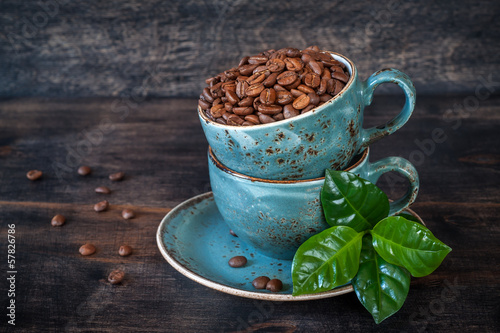 Roasted coffee beans with green leaves in cups