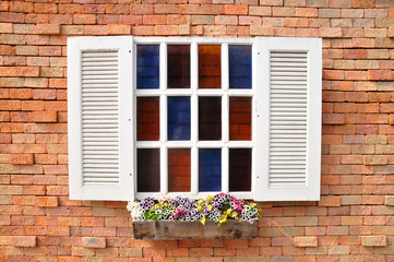 White window on red brick wall and color glass hang flowers pot.