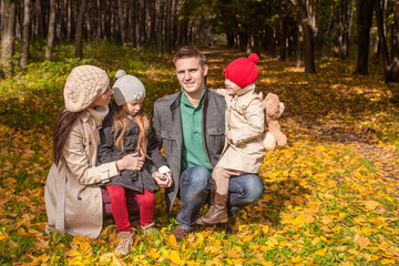 Adorable family of four enjoying a wonderful sunny autumn day in
