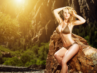 sexy blond in bikini posing on rock