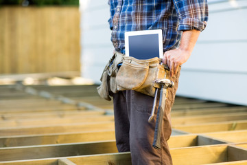 Construction Worker With Tablet Computer And Hammer In Toolbelt