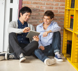 Students Using Digital Tablet While Sitting By Bookshelf In Libr
