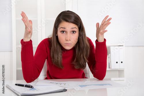 Hilflose junge Frau im Büro - gestresst und frustriert