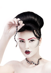 Woman with creative make up and snake in her hands