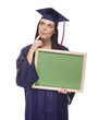 Thinking Female Graduate in Cap and Gown Holding Blank Chalkboar