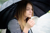 womanl drinks fragrant coffee with pleasure under umbrella poster