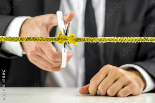 Businessman cutting yellow rope