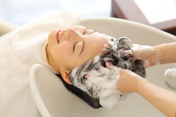 シャンプー台で髪を洗う女性