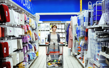 woman looking at household items in supermarket