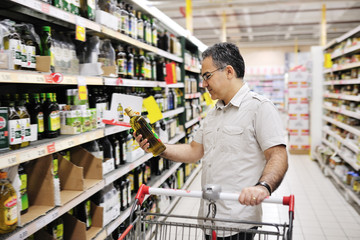 man shopping and looking at food in supermarket