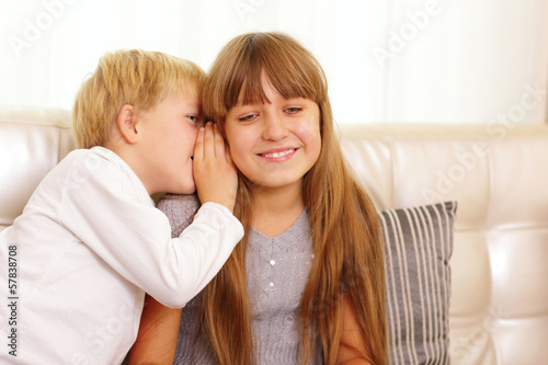 boy whispers something to his sister