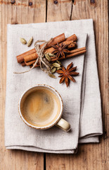 Coffee with spices on textured background