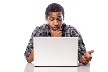 dark-skinned young man puzzled looking at his laptop