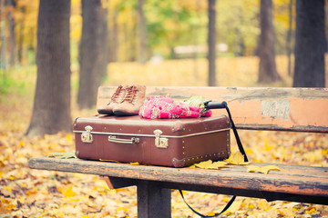 vintage suitcase, scarf, boots and umbrella on bench