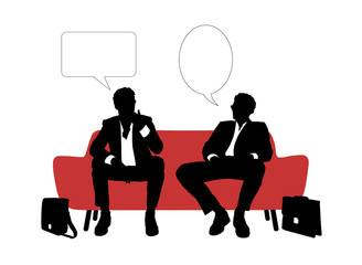 two businessmen speaking seated on red sofa