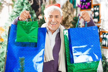Man Carrying Shopping Bags In Christmas Store
