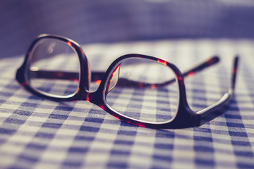 Pair of glasses on a checkered table cloth