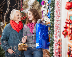 Mother And Daughter Shopping In Christmas Store