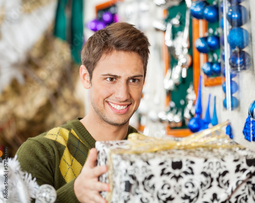 Man Holding Christmas Present In Store