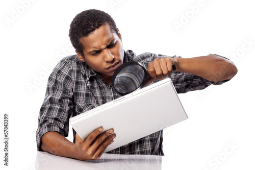 african man carefully looking on the back side on his laptop