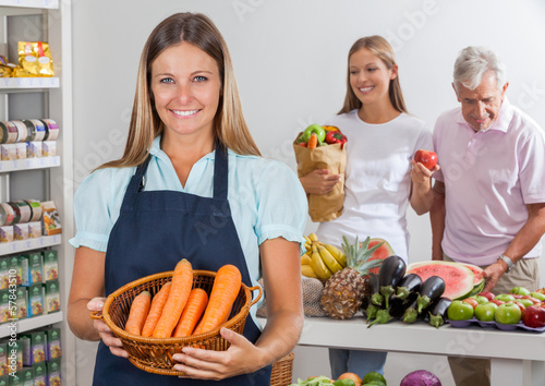 Saleswoman Holding Carrot Basket At Supermarket