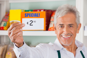 Happy Male Owner Showing Discount Sign In Store