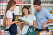 Saleswoman Assisting Couple In Buying Groceries