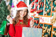 Woman In Santa Hat Carrying Shopping Bags
