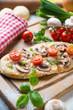 Mini-Pizza mit Champignons und Tomaten