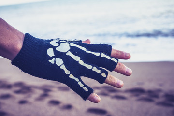 Woman wearing skeleton glove on the beach