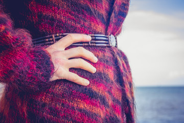 Close up on woman in woolen jumper on the beach