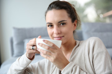 Peaceful woman relaxing at home with cup of tea