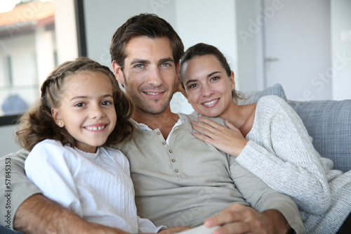Cheerful family of three relaxing in sofa