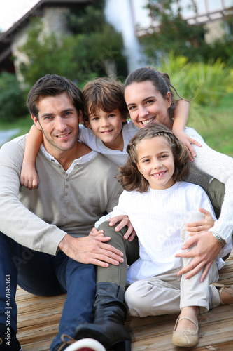 Parents with kids relaxing in front of home