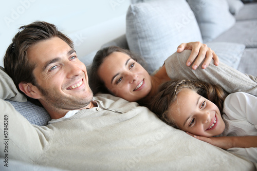 Parents with little girl laughing in couch