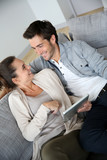 Cheerful couple sitting in sofa and using tablet