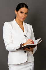 businesswoman in a white suit with a notebook