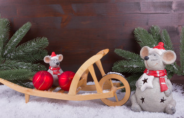 Mäuse mit Weihnachtskugel auf Karre im Schnee