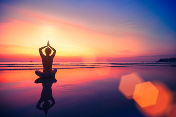 Silhouette yoga woman sitting on sea coast at beautiful sunset.