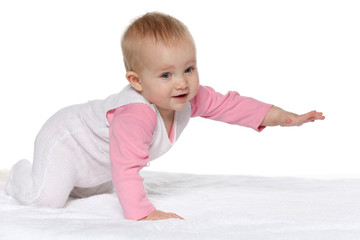 Active baby girl on the white towel