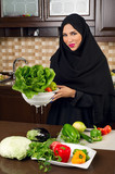 Arabian woman holding a bowl of veggies for salad preparation