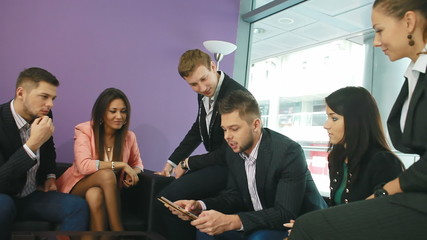 Group of business people applauding attractive man with tablet