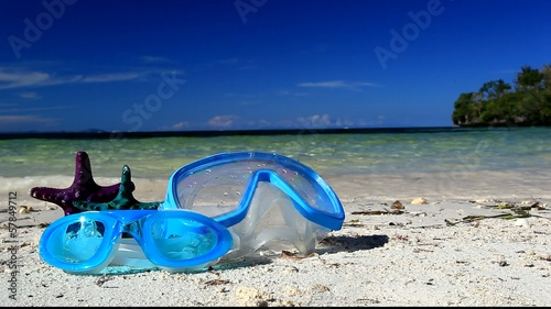 Swimming mask and starfish on tropical beach