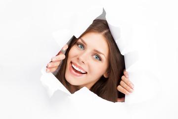 Young woman breaking through a paper sheet