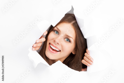 Young woman breaking through a paper sheet