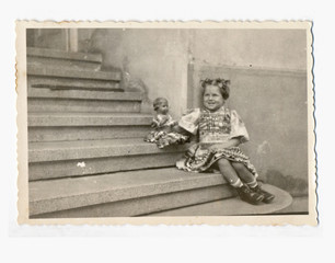 Little girl with doll on the stairs - circa 1950