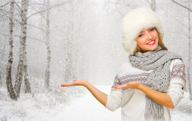 Young girl shows welcome gesture at snowy forest